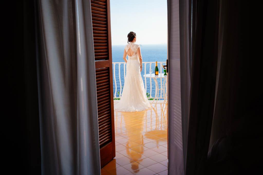una sposa si gode il panorama dall'hotel tramonto d'oro a praiano